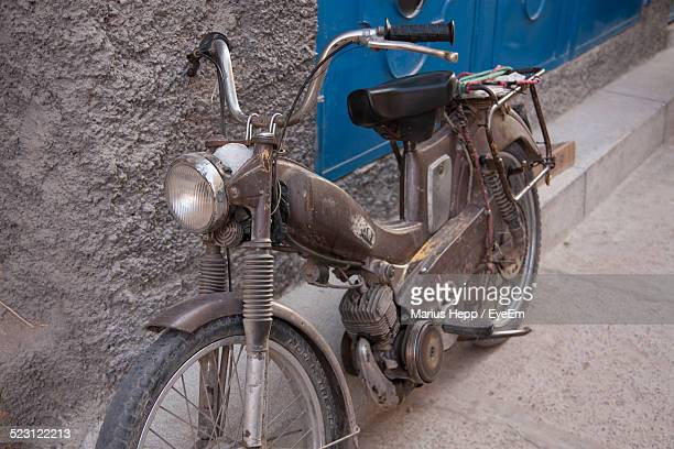 old moped leaning against a wall - moped stock photos and pictures