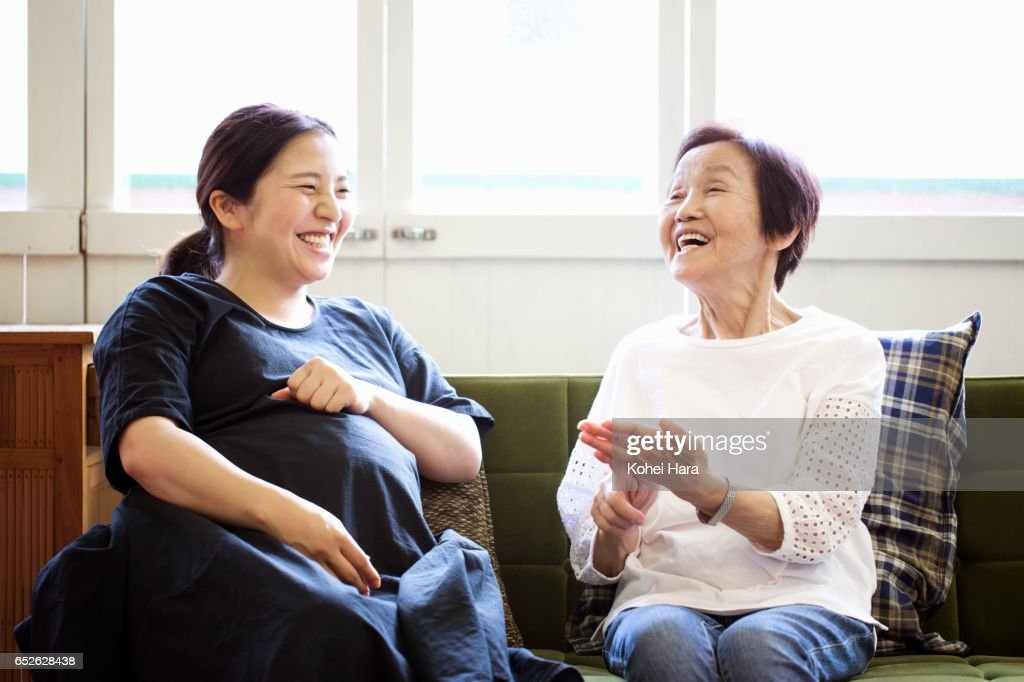 Old mother in her 80's and pregnant daughter in her 30's talking and laughing on sofa at home : Stock Photo