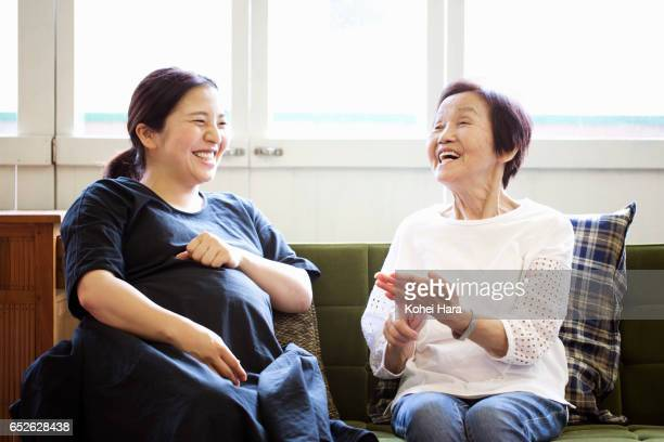 Old mother in her 80's and pregnant daughter in her 30's talking and laughing on sofa at home