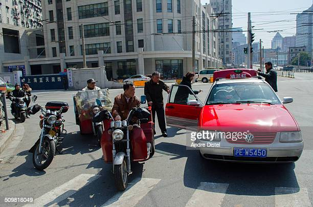 Old motorbikes and taxi stopping in the middle of the road in Shanghai to unload luggage.