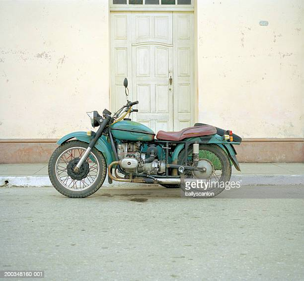 old motorcycle on street, side view - vintage motorcycle stock pictures, royalty-free photos & images