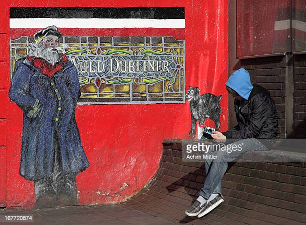 Old mural painting at an Irish Pub and young reader in Temple Bar District