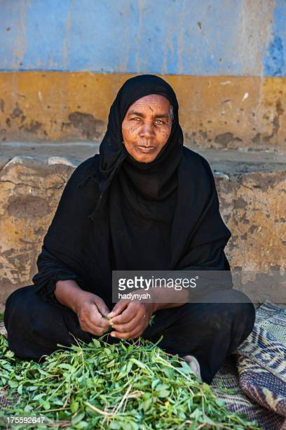 Old Muslim woman sorting spinach in Southern Egypt