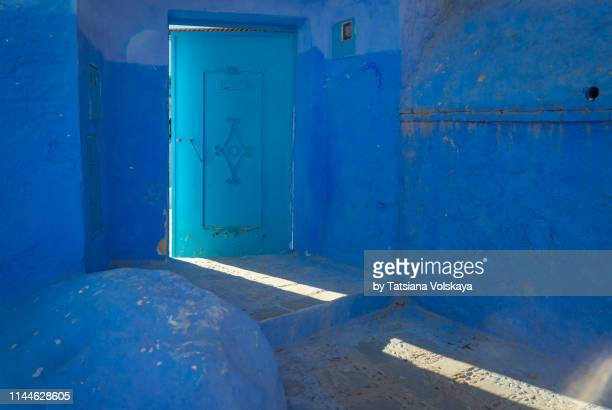old narrow street with light beam and opening door in blue city chefchaouen, morocco - easter religious background stock pictures, royalty-free photos & images