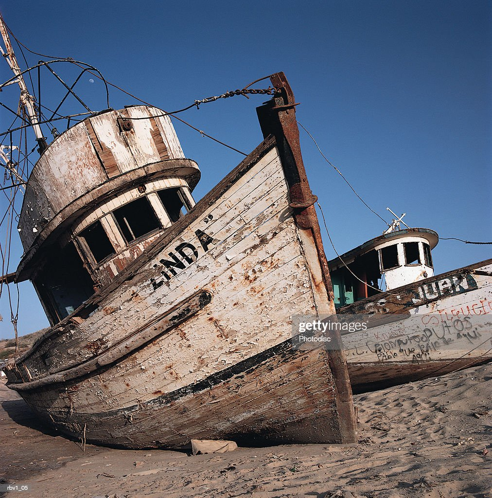 old neglected boats sit beached on sand under a blue sky : Foto de stock