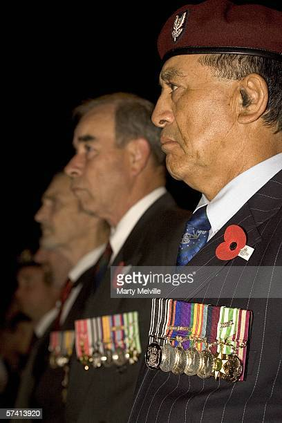 Old New Zealand soliders stand to attention with a crowd hundreds behind them as they listen to the service during the dawn ceremony of remembrance...