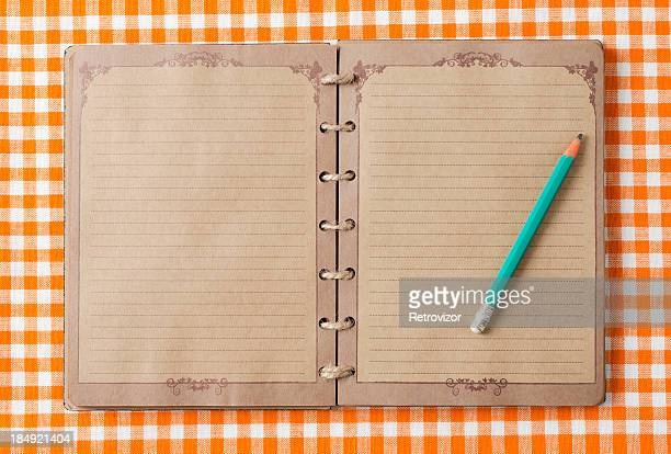 Old notebook and pencil on orange tableclot