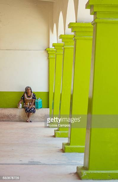 Old oaxacan woman sitting on a building corridor with Green columns in the city of Mitla Oaxaca Mexico