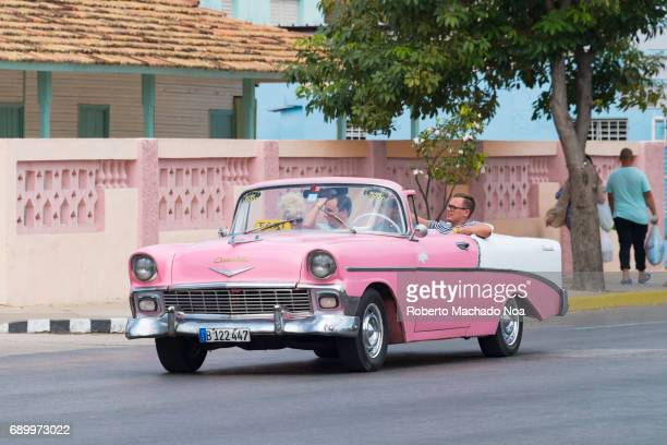 Old obsolete American car in use Passenger traveling in a pink convertible taxi on a quiet road