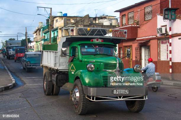 Old obsolete American truck driving in the city traffic during the rush hours