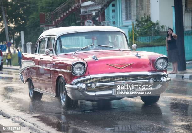 Old obsolete pink Chevrolet 1957 American car in urban areas Cuban transportation and lifestyle in rainy day
