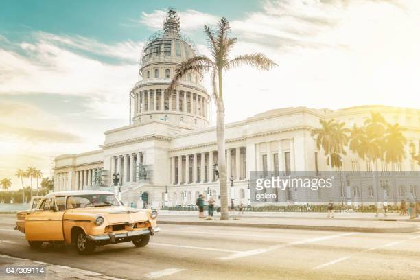 old orange american car in front of capitol in havanna - old havana stock pictures, royalty-free photos & images