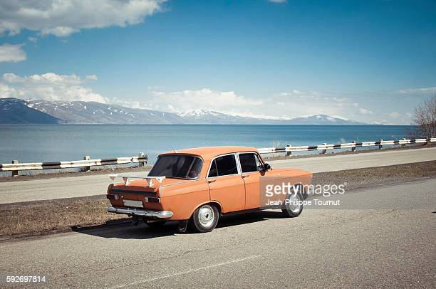 old orange car near sevan lake in armenia - vintage car stock pictures, royalty-free photos & images