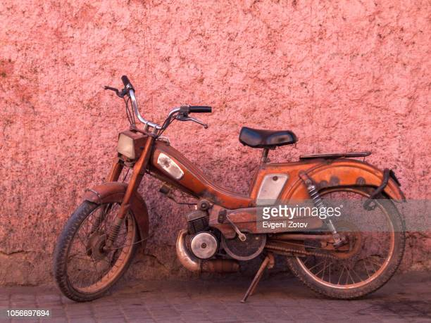 old orange moped in front of pink wall in marrakesh, morocco - moped fotografías e imágenes de stock