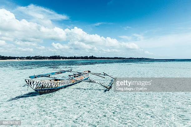 old outrigger boat moored in lagoon against sky - mombasa stock photos and pictures