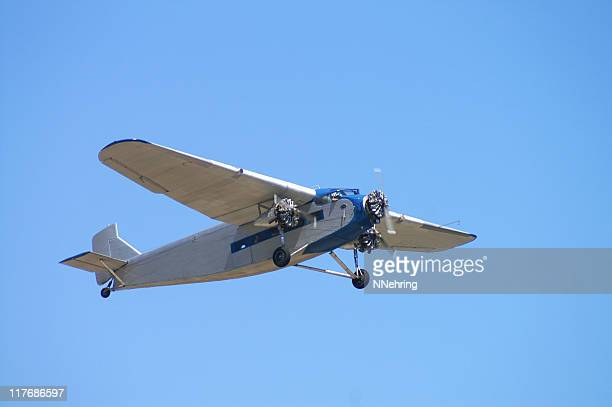 old passenger airplane ford trimotor flying in clear blue sky - 1920 1929 stock pictures, royalty-free photos & images