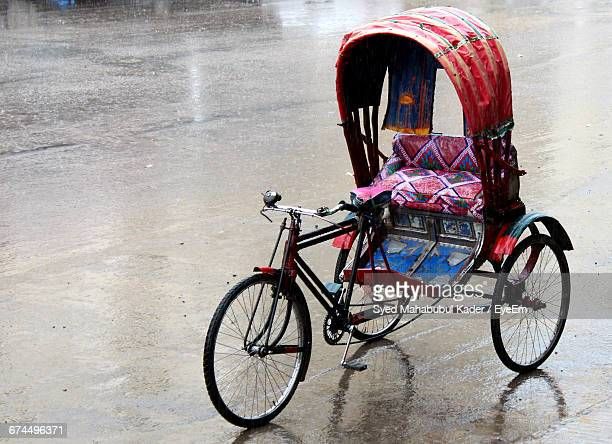 old pedicab on wet road - rickshaw stock photos and pictures