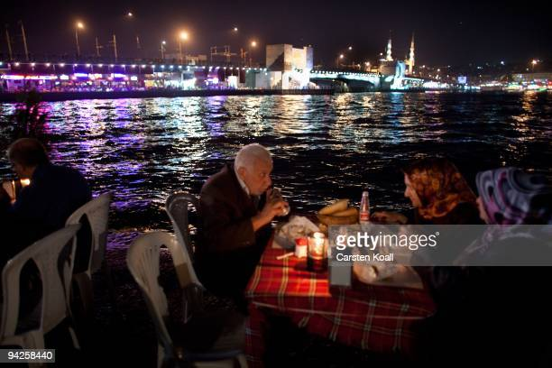 Old people have a dinner at the riverside close in the back the Galata Bridge on October 19, 2009 in Istanbul, Turkey. The Turkish metropolis on the...