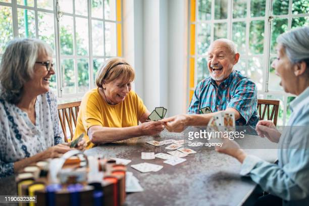 old people having fun playing cards in nursing home - retirement community stock pictures, royalty-free photos & images