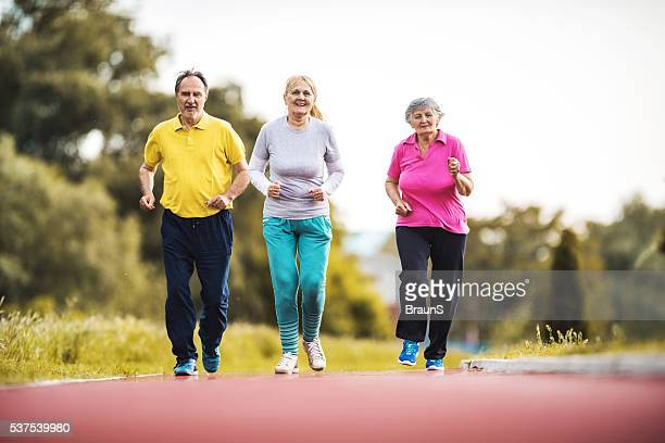 Old people running together on a sports track outdoors.