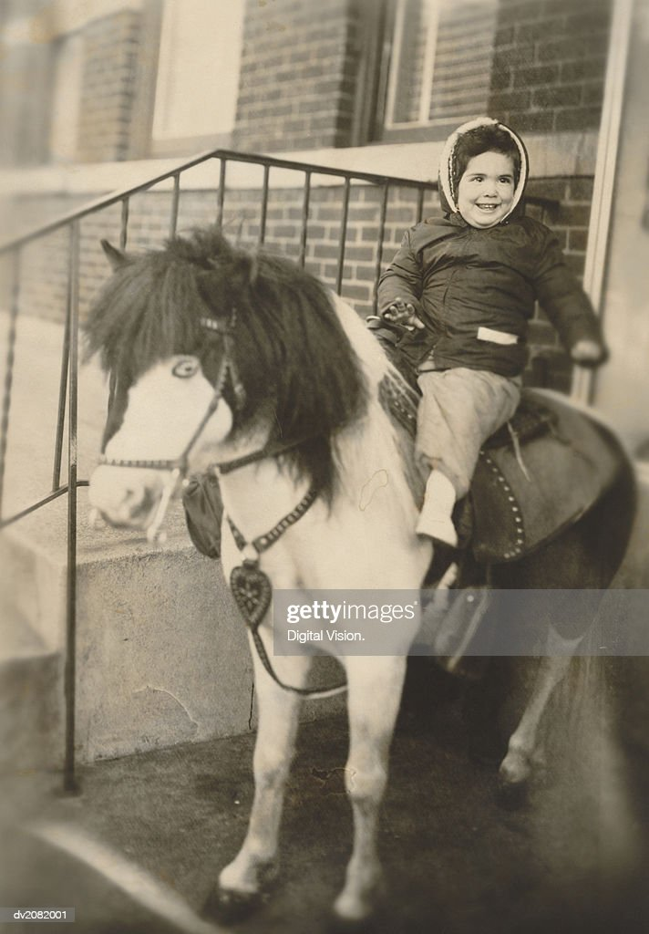 Old Photograph of a Young Girl Sitting on a Pony on Her Doorstep : Stock Photo