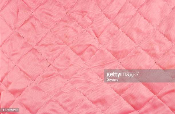 old pink quilted satin background. - stiches stock photos and pictures
