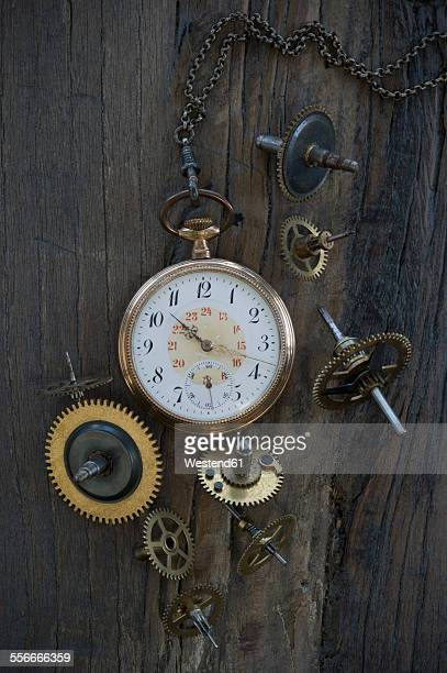 Old pocket watch and cogwheels on dark wood