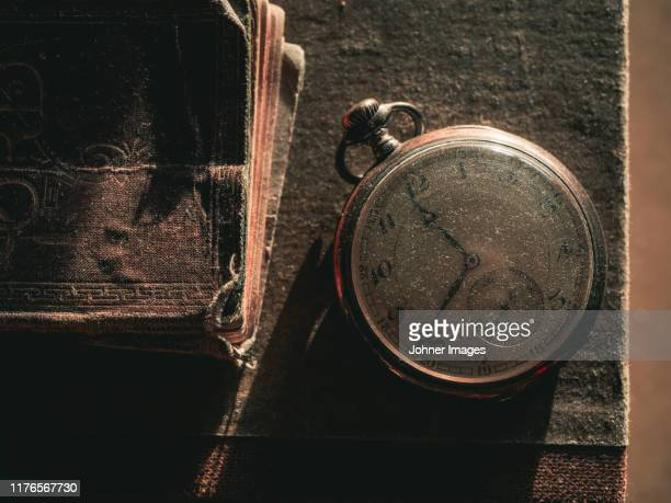 old pocket watch on book - small group of objects stock pictures, royalty-free photos & images