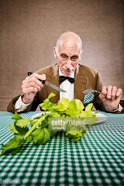 Old poor man eating a humble meal.
