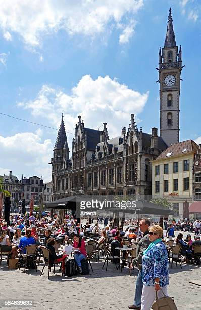 Old post office and tourists at pavement cafe on the Korenmarkt / Wheat Market in summer in Ghent Belgium