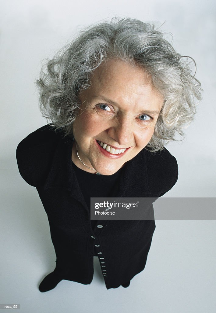 old pretty caucasian adult female with white curly hair and blue eyes wears a dark trendy sweater dress and looks up at the camera smiling warmly : Foto de stock