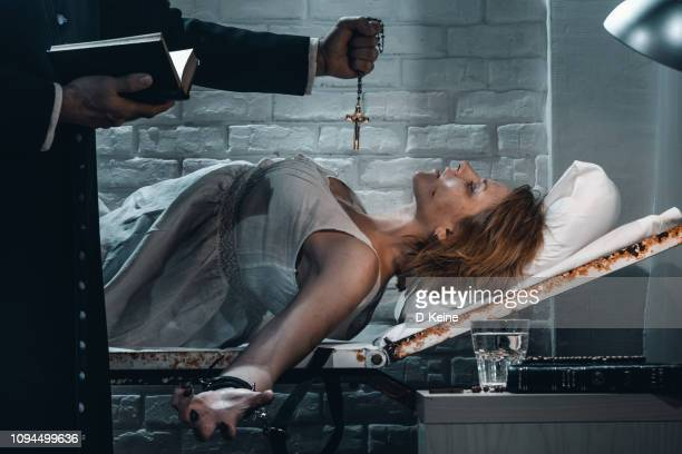 old priest performing exorcism ritual of young possesed woman - catholic easter stock pictures, royalty-free photos & images