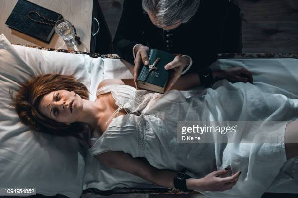 old priest performing exorcism ritual of young possesed woman - cerimónia imagens e fotografias de stock