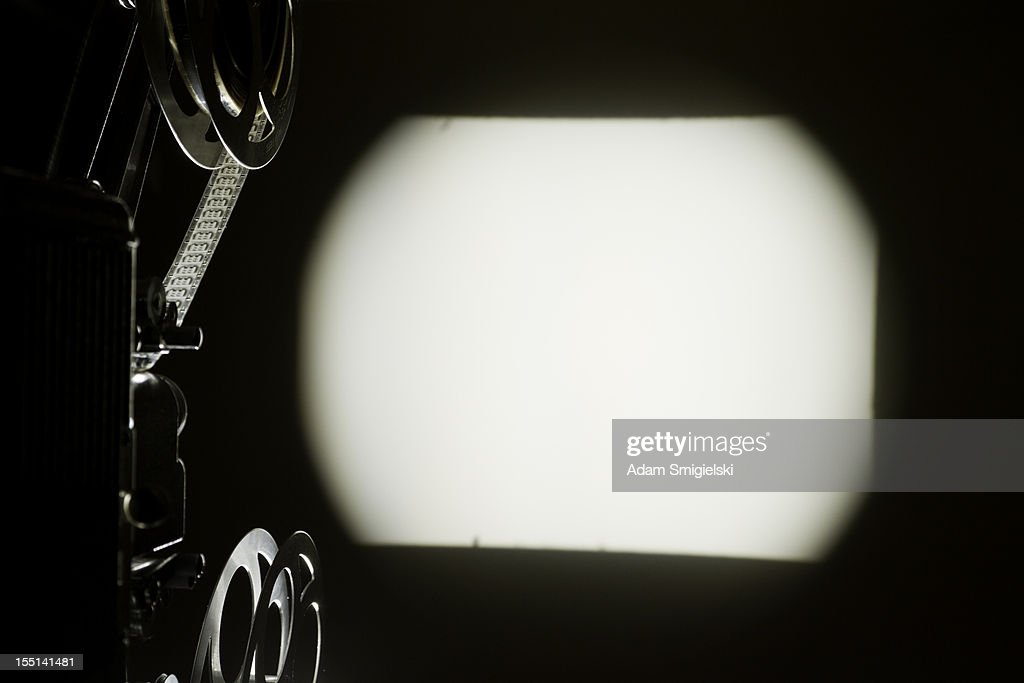 old projector with blank screening on the wall : Stock Photo