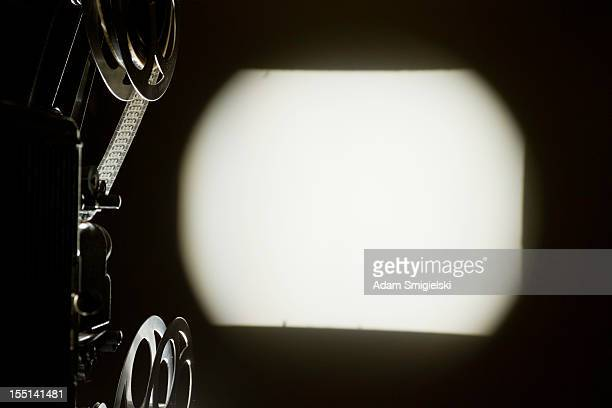 old projector with blank screening on the wall - spotlight film stock photos and pictures