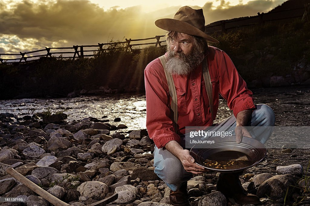 Old Prospector Panning For Gold In A Western Sunset : Stock Photo