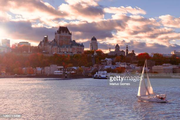 old quebec city at sunset with sailboat in foreground - ケベック州 ストックフォトと画像