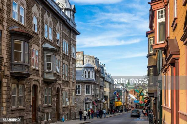 Old Quebec city street scene, where historical buildings and people are visible in the image.