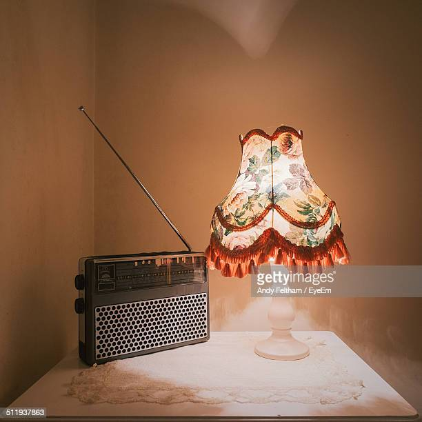 Old radio by lit lamp