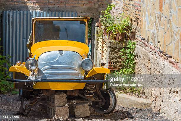 Old rare vintage car reparation in alley between two houses This car might be used as tourist taxi in the future Cubans allot a lot of value to old...