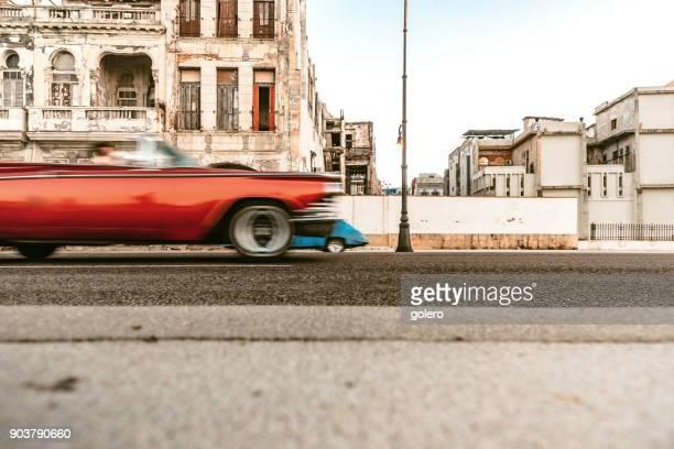 alte rote amerikanische Oldtimer am Malecon vor verwitterte Häuser
