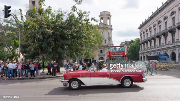 Old red and white Buick vintage car drives in Central Park, Havana