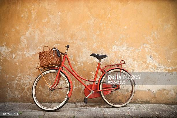 Old red bike against a yellow wall in Tuscany, Italy