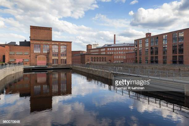 old red brick industrial buildings along the tammerkoski rapids in downtown tampere, finland on a sunny day. - タンペレ ストックフォトと画像