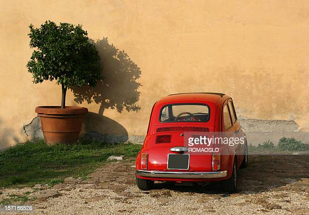 Old red mini under a tree in Rome Italy