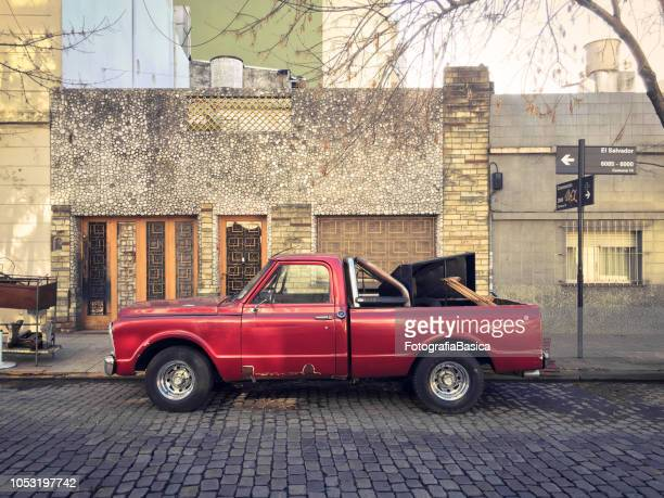 Old red pick-up truck parked in the street
