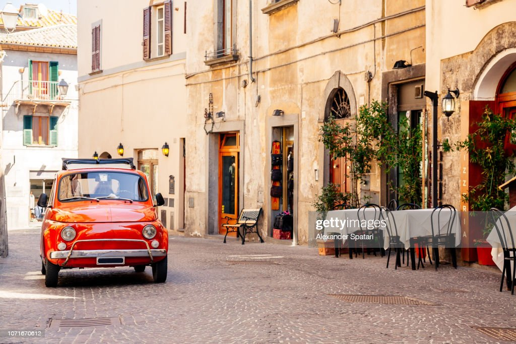 Old red small vintage car on the street of Italian city on a sunny day : Stockfoto