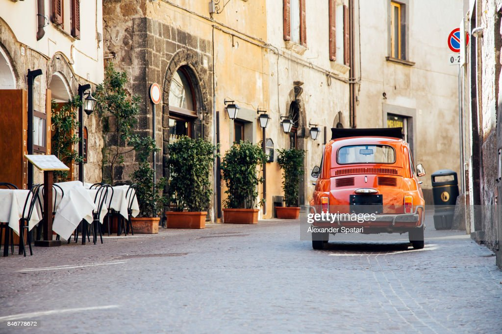 Old red vintage car on the narrow street in Italy : Stock-Foto