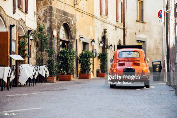 old red vintage car on the narrow street in italy - mediterrane kultur stock-fotos und bilder
