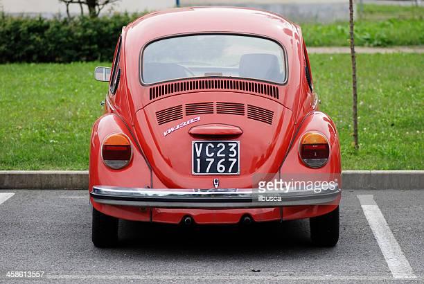 old red volkswagen beetle in the street - volkswagen beetle stock photos and pictures